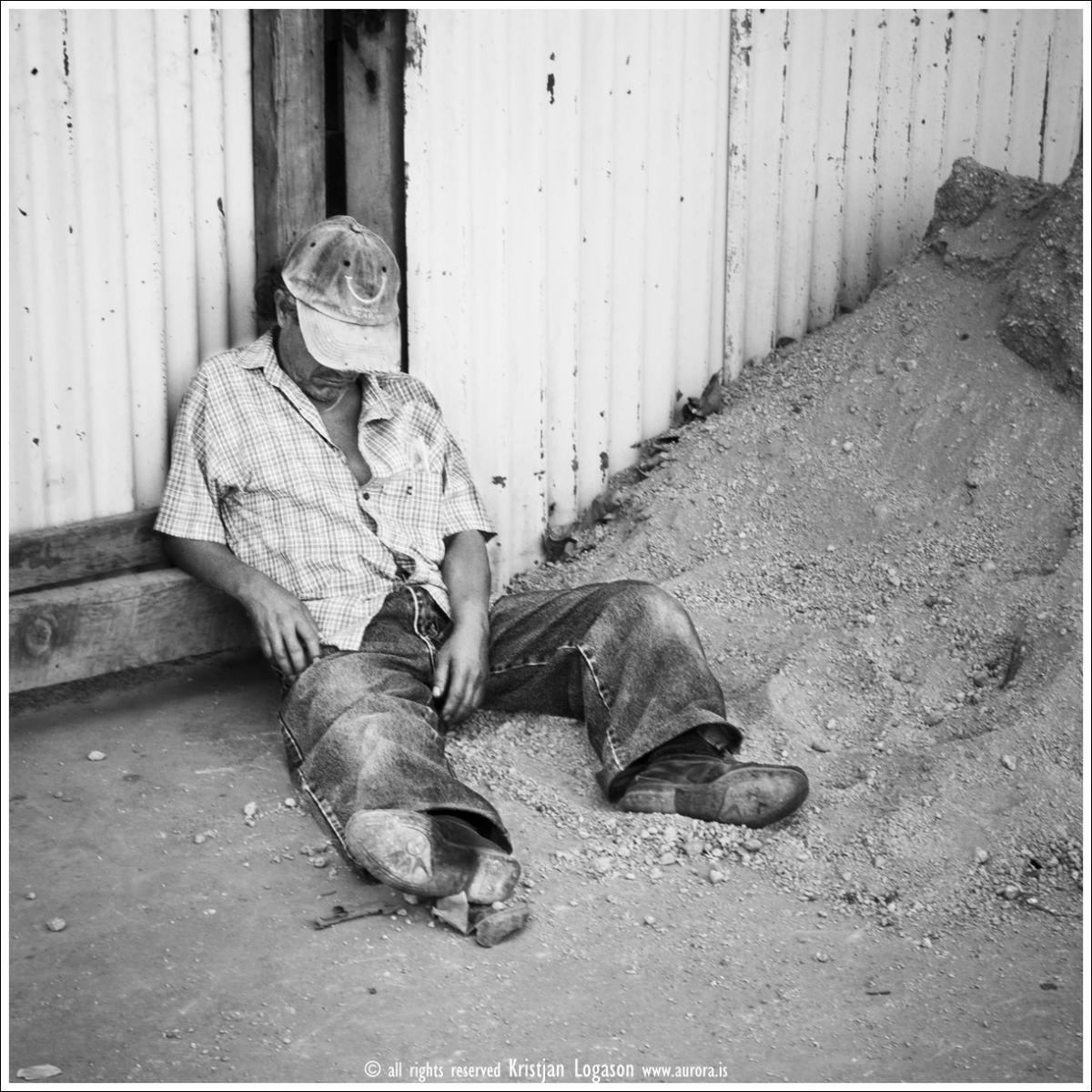 Tired man sleeping on the sidewalk i Juayua El Salvador
