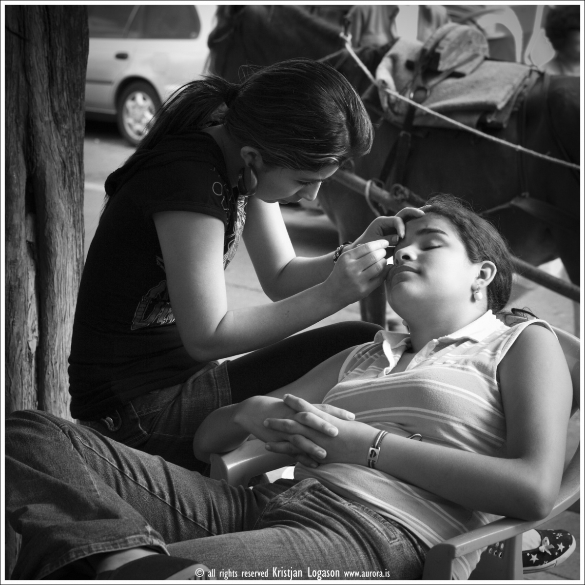 Young woman plucking the eyebrows of an other at the square in Juayua, El Salvador