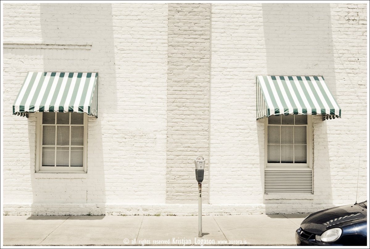 White painted brick building and a parking meter and a car front