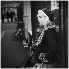 Young stylishly dressed blonde woman standing infront of a shop window in Amsterdam