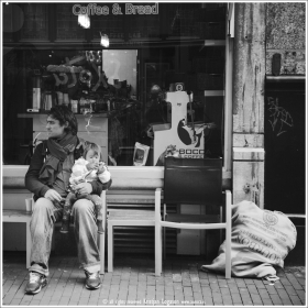 Man with child in his arms sitting out side a coffee shop in central Amsterdam