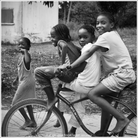 Three girls in Gales point Belize, riding on one bicycle