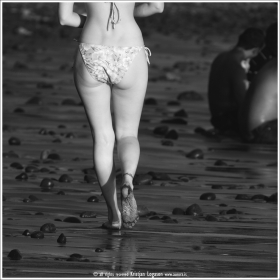 Woman in bikini walking on the beach of El Tunco in El Salvador