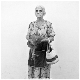 Old woman with chicken in here hands coming from shopping at the market in Suchitoto - El Salvado